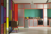 A stained-glass sliding door treatment in a tangerine-trimmed Paris kitchen