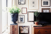 A gallery wall of art surrounding a wooden chest topped with a TV