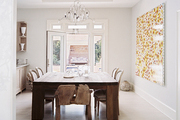 A wooden dining table balanced by large-scale floral art