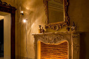 A fireplace mantel with a gilt-framed mirror and contemporary floor lamps