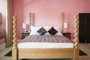 A barley-twist four-poster bed in a pink guest room