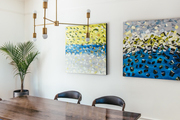 A contemporary dining space with blue and yellow paintings.
