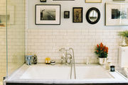 Framed art and white subway tile above a large bathtub