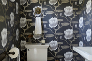 The half-bathroom is accented with classic additions and wallpaper.
