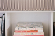 Vintage design books are artfully stacked below a ticking-stripe window seat.