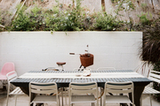 An outdoor dining table surrounded by white chairs