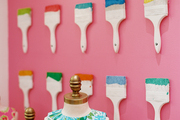 Paintbrushes on display against a pink background