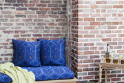 A vibrant love seat set against a brick wall