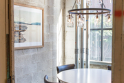Exposed brick wall aside small seating area.