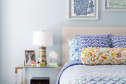 A tiered bedside table in a pattern-filled bedroom