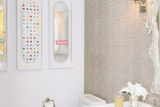 A bathroom with chevron tile and framed Damien Hirst skateboards