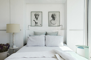 Vintage art hanging above striped linen bed.