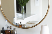 Round mirror hanging over a small table