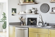 A kitchen with yellow cabinets and artwork on gloating shelves.