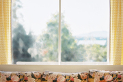 A floral couch beneath a window outfitted with yellow patterned curtains