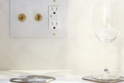 Gold switches and electric outlets on white wall.