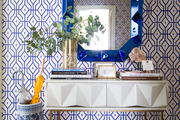 Vivid patterned wall behind blue mirror and white dresser.