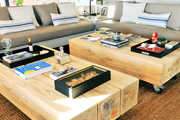 A pair of wooden coffee tables and beige sofas.