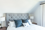 A contemporary bedroom with a tufted gray headboard.