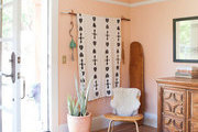 An entryway with coral walls and Bohemian accents.