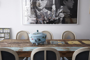 Vintage distressed wood table and chairs in front of large-scale art.