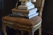 A vintage phone on a stack of books on an antique chair with leopard slippers