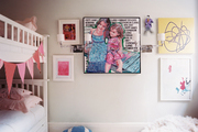 Framed art and a white bunk bed in a children's bedroom