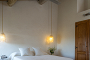 Exposed beams and terra-cotta tile in a minimalist bedroom
