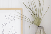 Abstract wall art with pottery and a plant beside it.