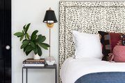 A contemporary bed with patterned headboard.
