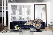 A gallery wall of framed artwork behind a tufted couch in an industrial-style loft
