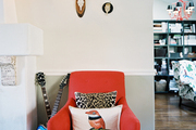 A grouping of antlers hung above a red upholstered armchair with a leopard-print pillow