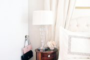 A round bedside table next to a tufted headboard