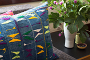An embroidered pillow and a vase of flowers