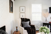 A white wingback chair with a fur throw beside a round end table