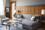 Tall wood wainscoting surrounding grey furniture in cozy living room.