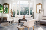 Upholstered furniture and gilded mirrors in a white-walled living space