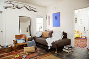 A comfortable living area with a tribal rug and leather chair.