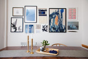 A gallery wall hangs above a candlestick-topped dining table