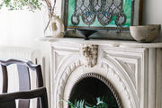 A marble fireplace with a stained glass window.