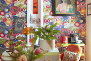 Floral patterned wallpaper to match the orange seating chairs and yellow coffee bar.