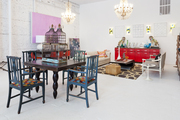 An antique birdcage on a dining table next to a seating area and a red console at Buckingham Interiors + Design