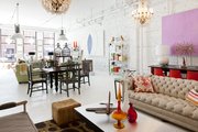 A chesterfield sofa, ottoman, and dining table at Buckingham Interiors + Design