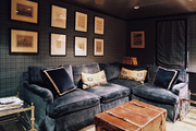 A blue sectional couch and a leather trunk atop leopard-print carpeting