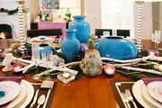 A dining table decorated for the holidays with blue vases and branches