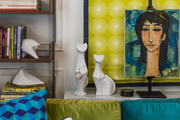 A painting and a framed print, a colorful couch with throw pillows, and a bookcase