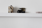A spare vignette displayed on a wall shelf in a minimalist space