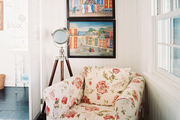 A floral armchair with an industrial light fixture and framed art