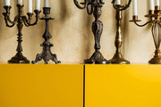 Vintage candelabras on a contemporary yellow shelving unit