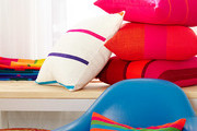 Bright pink and red pillows and blue chair.